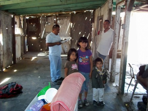 Juan from EOC with Roberto and his kids in their original home